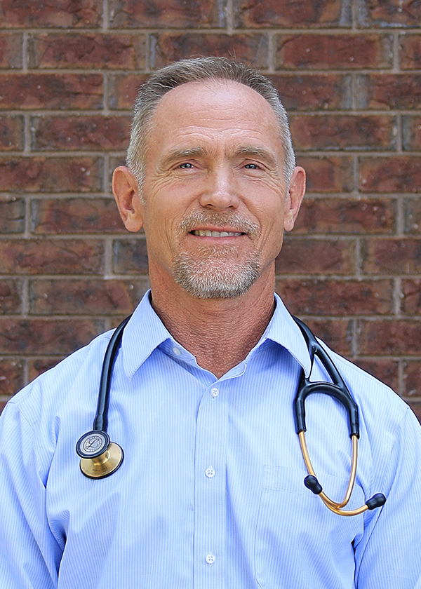 Dr. Stuart Porter DO, professional head shot smiling in front of red brick building