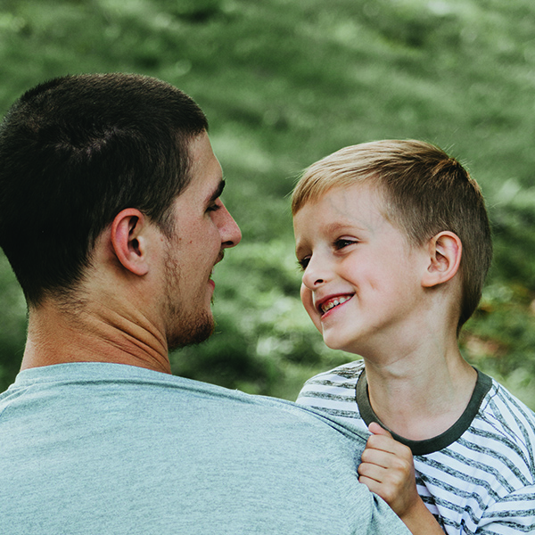 Father holding young son in arms while they smile at each other
