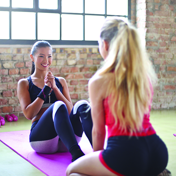 Two women in workout clothes exercising in gym with weights and yoga mat