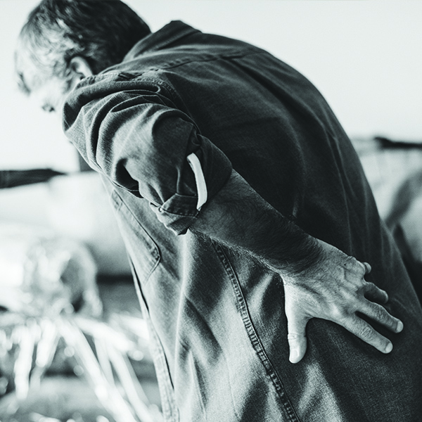 Middle-aged man hunched over in pain grabbing back