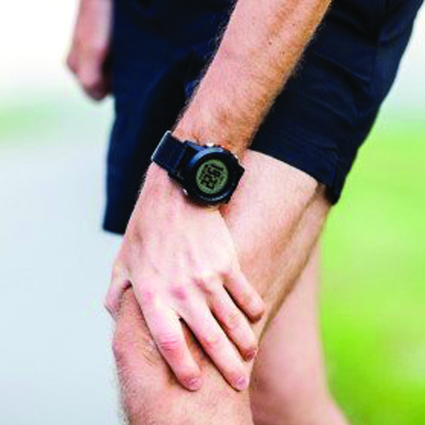 Man holding knee in pain with athletic clothes on